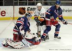 NEW YORK, Feb. 19 � New York Rangers goaltender Mike Dunham tries to cover the loose puck as Greg de Vries (4) battles New York Islanders center Justin Papineau, Thursday night, during a 6- ...